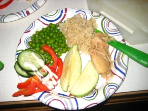 Pineapple chicken with brown rice, peas, cucumbers with red bell peppers drizzled with ranch, and apple slices